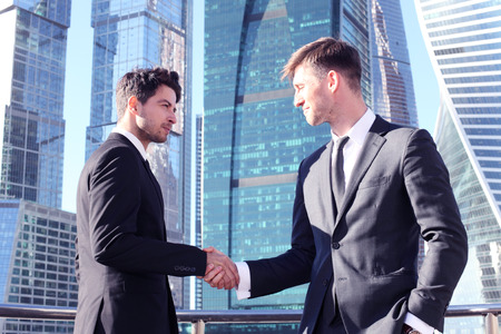 corporate buildings: Business people shaking hands on skyscraper background Stock Photo