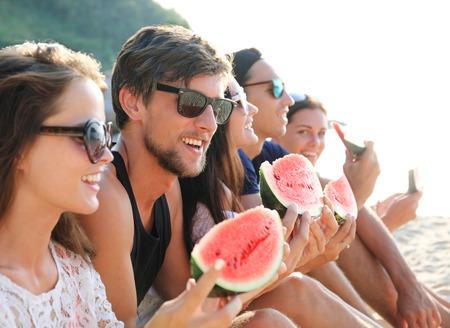 Happy young friends eating watermelon on beach Standard-Bild