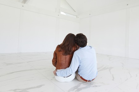 Paar sitzt an ihrem neuen leeren Wohnung