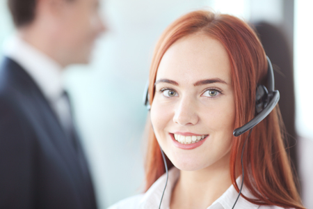 earpiece: Portrait of a smiling creative businesswoman with earpiece in office Stock Photo