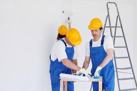 builder: Equipo de constructores con el plan de construcci�n en interiores Foto de archivo