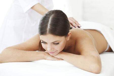 getting: Young beautiful woman in spa getting hot stone massage Stock Photo