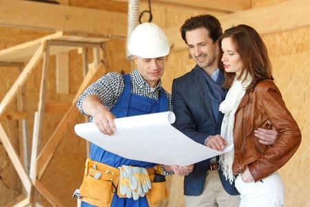 Pracovník ukazuje konstrukce domu plány mladého páru na staveništi