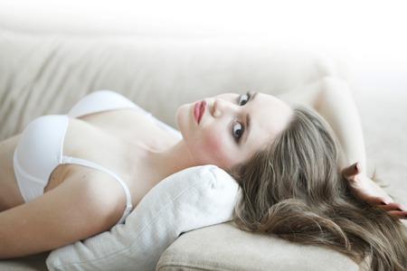 ropa interior niñas: Retrato de la hermosa mujer joven en ropa interior en el sofá