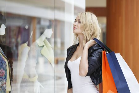 showcase: Woman with paper bags looking at showcase in shopping mall Stock Photo