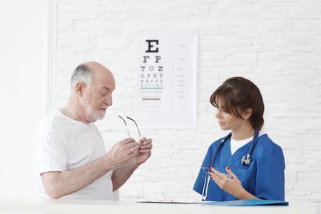 examen de la vista: Doctor que hace la prueba de la visión de nuevos vasos