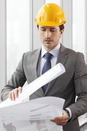 architector: Architector in hardhat and business suit with construction plans Stock Photo