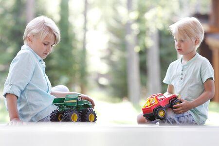brothers playing: Los hermanos peque�os jugando con coches de juguete al aire libre Foto de archivo