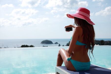 tourist resort: Beautiful woman relaxing by the pool at tourist resort Stock Photo
