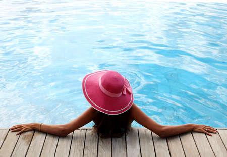 tourist resort: Beautiful woman relaxing at swimming pool at tourist resort