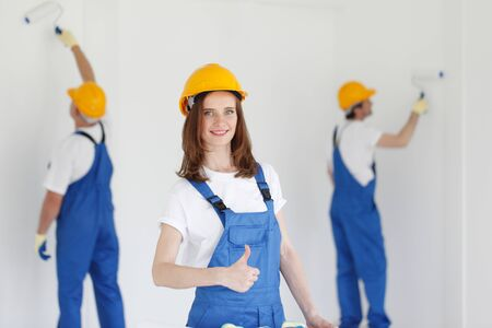 Workman gives thumbs up in front of two painters Stock Photo