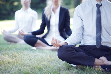 Business people practicing yoga in park 写真素材