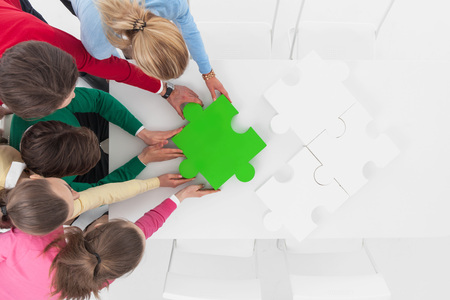 informal clothing: Group of people assembling jigsaw puzzle sitting around white table