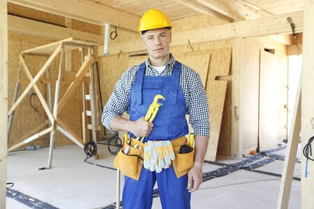 Workman with wrench inside wooden house under construction