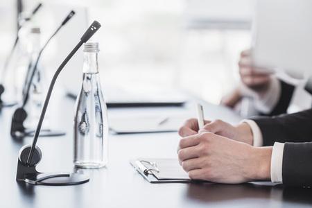 Microfoons op tafel in vergaderzaal en zakelijke man handen
