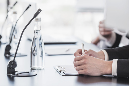 Microphones on table in conference room and business man hands Standard-Bild