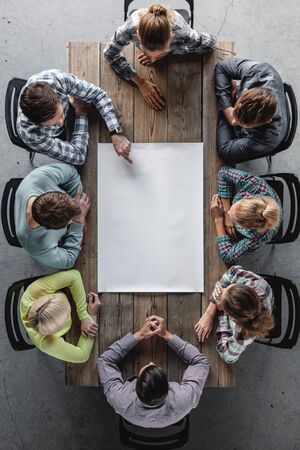 Hipster business teamwork brainstorming planning meeting concept, people sitting around the table with white paper Standard-Bild