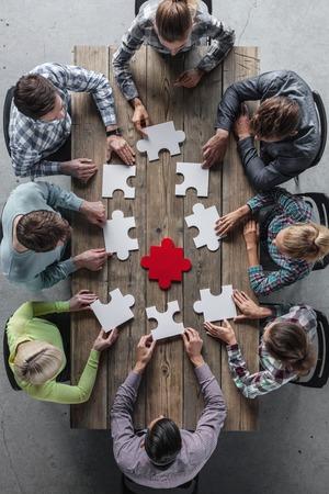Hipster business successful teamwork concept, business group assembling jigsaw puzzle Foto de archivo