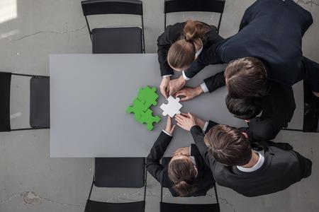 Groupe de gens d'affaires assembler puzzle et représenter le concept de soutien et d'aide de l'équipe