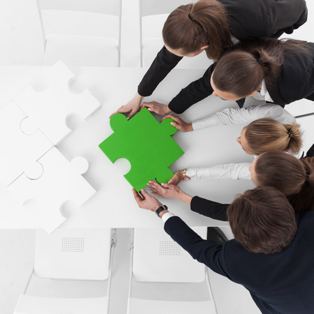business puzzle: Group of business people assembling jigsaw puzzle Stock Photo