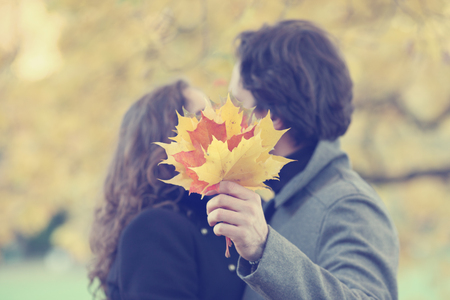 yellow trees: Happy couple kissing in autumn park with yellow trees Stock Photo