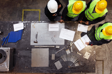 Team of workers and foreman look at documents and blueprints on table at factory