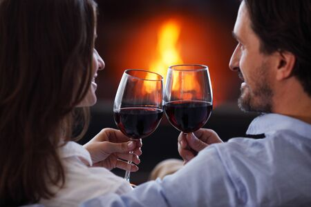 fireplace home: Romantic couple drinking wine at home near fireplace Stock Photo