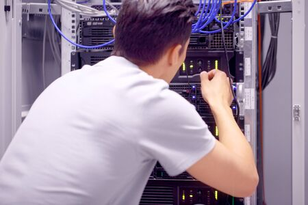 Young engeneer man in network server room connecting wires