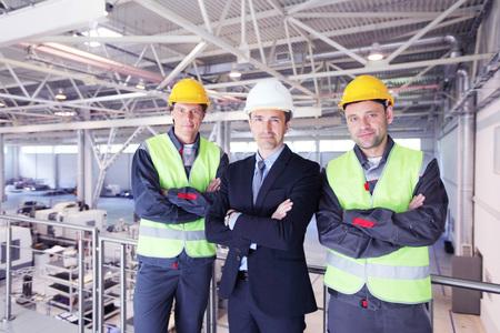 ingenieria industrial: Equipo de gerente y dos trabajadores en la fábrica CNC