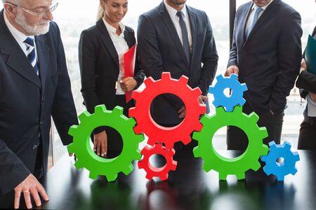 teamwork people: Business people assembling cogwheels, teamwork concept
