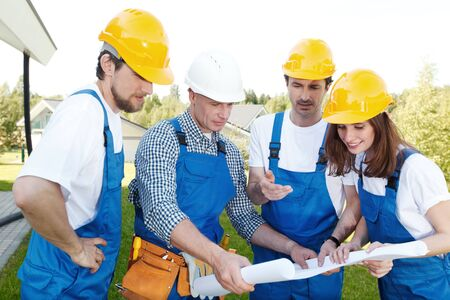 foremen: Team of builders with construction plan outdoors