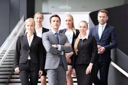 collaborators: Portrait of business people standing on the steps of stairs Stock Photo