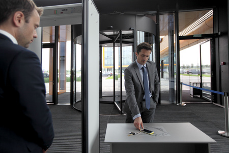 Mann, der am Flughafen Sicherheitstore Putting out Telefon und Schlüssel