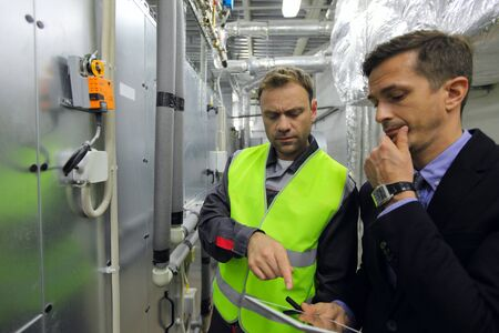 Worker and manager in electrical switchgear room of CNC plant