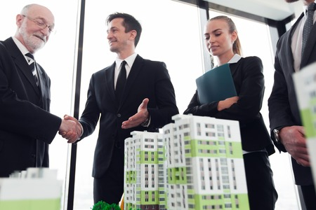Business meeting of architects and investors looking at model of residential quarter houses