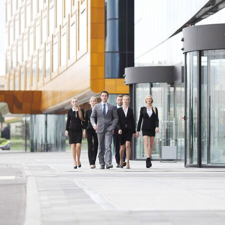 office buildings: Group of business people walking in down town near office building Stock Photo