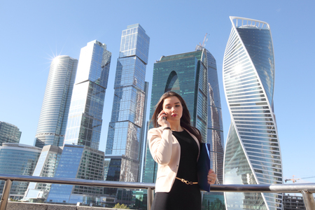 Young beautiful businesswoman with cellphone outdoors at skyscraper background Stock Photo
