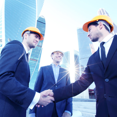 the view from below: Investor and contractor shaking hands, view from below