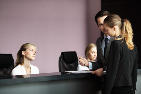 front desk: Business people filling forms at front desk Stock Photo