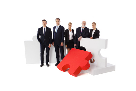 assembled: Business people team and assembled puzzle isolated on white background Stock Photo