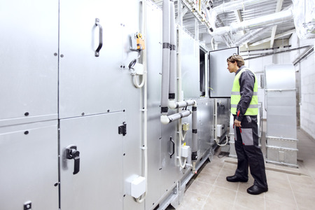 switchgear: Worker in electrical switchgear room of CNC plant