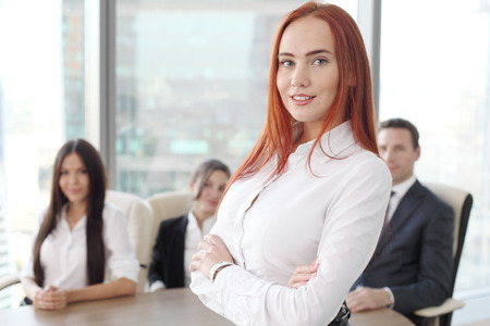 confidently: Group portrait of a professional business woman and team looking confidently at camera