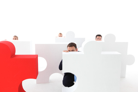 pices: Business people hiding behind puzzle pices