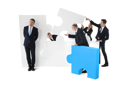 Lazy businessman and business team working concept, people assembling puzzle isolated on white Stock Photo