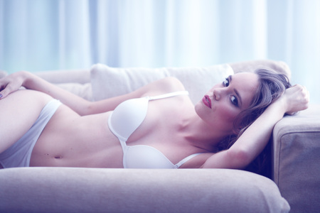 woman on couch: Portrait of beautiful young woman in lingerie on couch