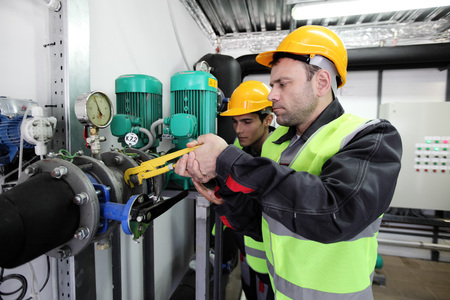 power wrench: Two workers fixing pipes with manometer on high pressure system at factory Stock Photo