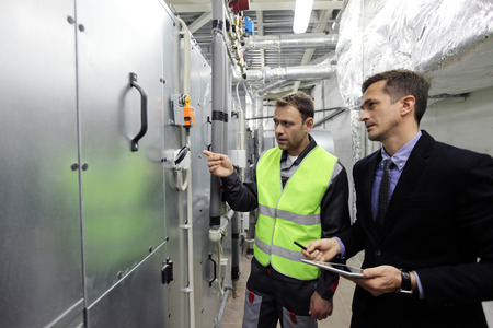 Worker and manager check switchboards at factory auxiliary room Standard-Bild