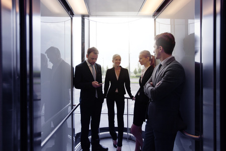 Business team going on elevator and talking