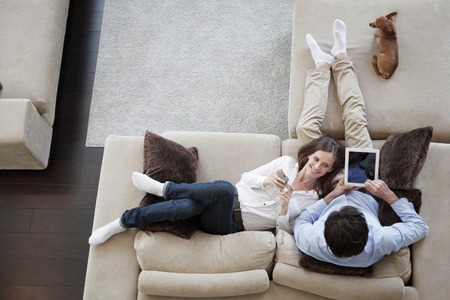 Couple using digital tablet at home sitting on sofa, top view Banque d'images