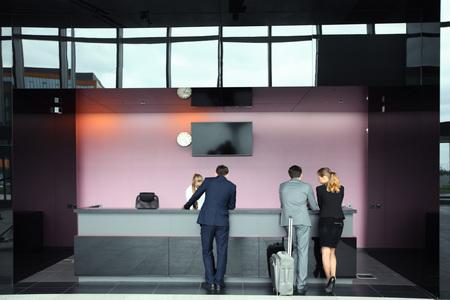 空港でチェックインのビジネス人乗客を待っているスーツケース